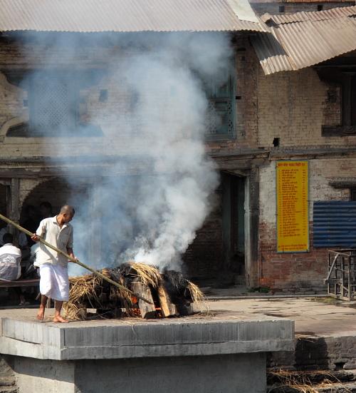 man tending cremation